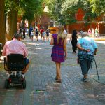 Man in Wheelchair, Woman with Cane, and Young Woman Walking