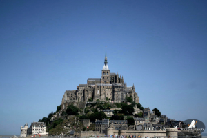 Image Description: The abbey of Mont St. Michel in France sits on top of a hill taking up most of the small island. A small village sits below the abbey.