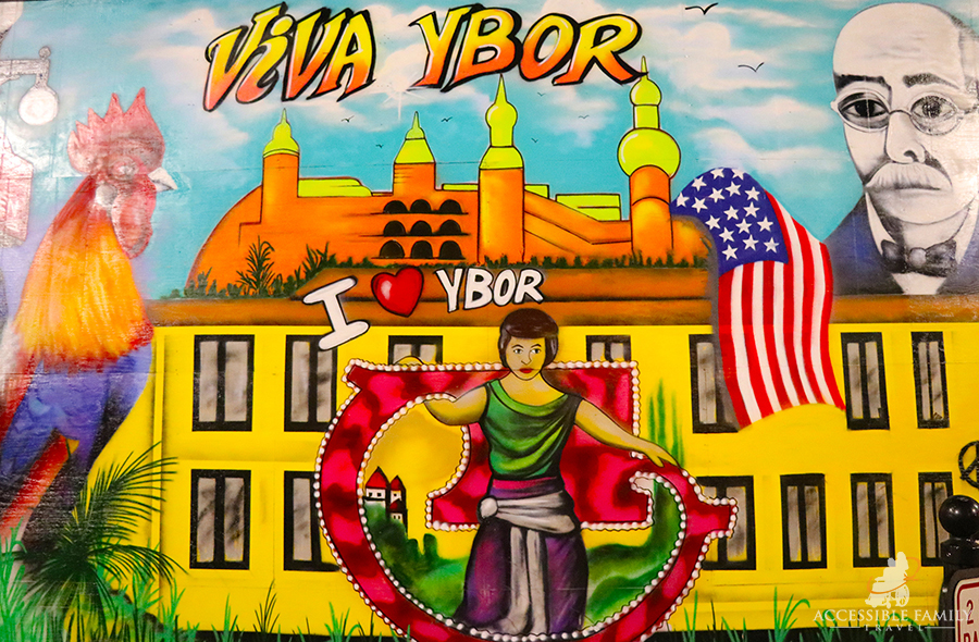 Image is of a vibrant mural of Ybor city painted on a building. A large rooster is on the left, a large yellow building in the front, a colourful dancer in front, with a mans image in the upper right corner.