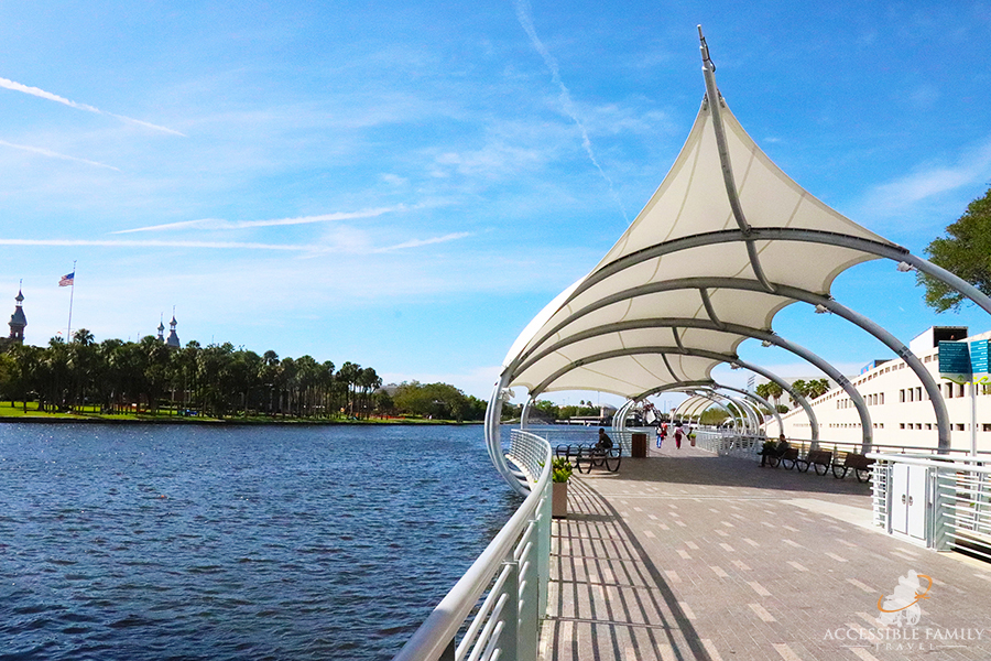 Image is of a view from along the Tampa Riverwalk. A wide path covered with an awning overlooks the river with a park on the other side.