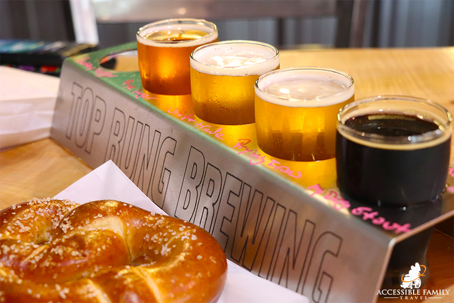 Image is of a row of 4 beers in tasting classes and a soft pretzel at Top Rung Brewing in Olympia, WA
