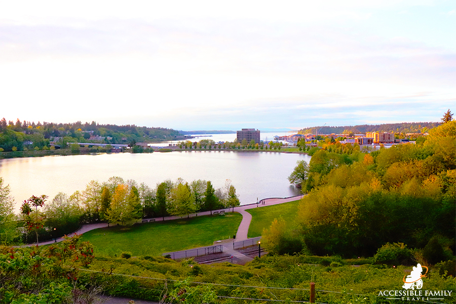 View is of the Heritage Park with two larger bodies of water separated by a road and buildings at the Heritage Park Trail in Olympia, WA .