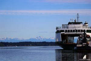 The images is of a ferry on the water on the right side. The background is blue sky on top, the Olympic Mountain Range stretching across the middle of the image, with water on the bottom.
