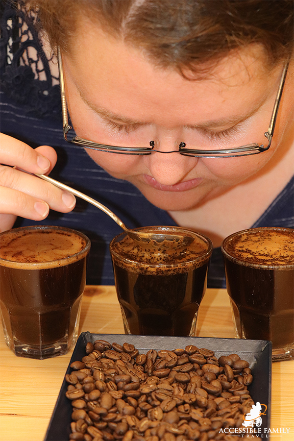 Women with glasses is leaned over three small glasses of coffee tasting them with a spoon at the Batdorf & Broson's Tasting Room. A small tray of coffee beans is in the forefront of the photo.
