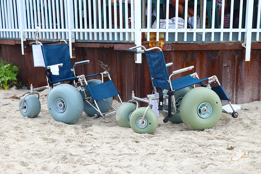 Two beach wheelchairs are lined up against a building on the beach.