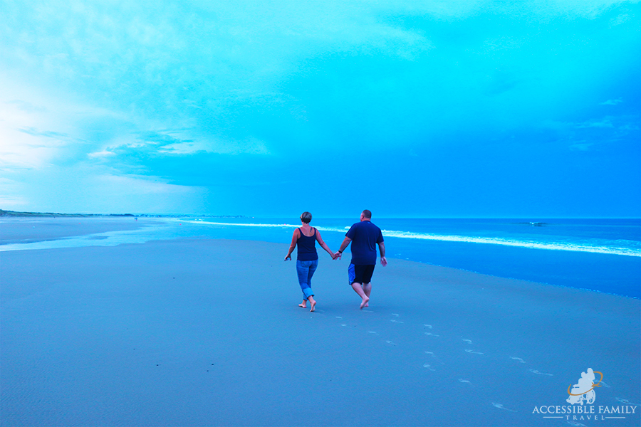 A man and woman walk on the beach holding hands leaving footprints in the sand after a summer rain storm.