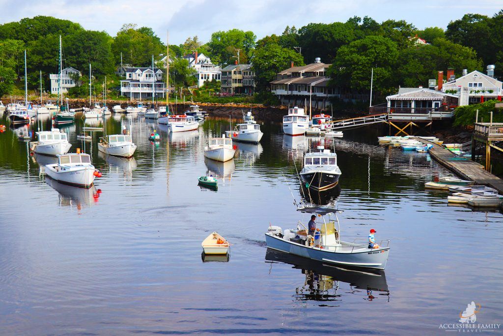 Many fishing boats dot the cove surrounded by houses in Perkins Cove. A small boy with a red hat is sitting on the front of a boat with a man steering in the first boat.